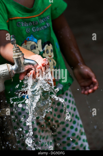 Young Indian girl / infant playing with water from a tap in a rural Indian village. Andhra Pradesh, India - Stock Image