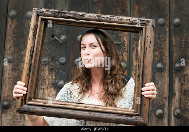 Portrait of mid adult woman, holding wooden frame in front of face, Mexico City, Mexico - Stock-Bilder