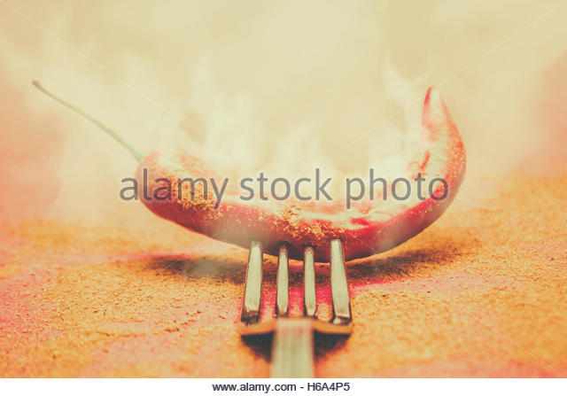 Artistic retro kitchen artwork on a smoking hot red chilli pepper on mexican restaurant fork. Organic heat - Stock Image