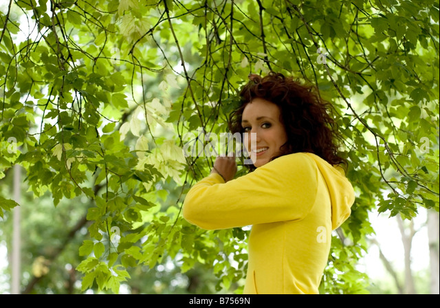 Young woman holding branches, Winnipeg, Canada - Stock Image
