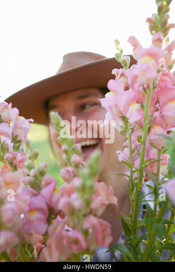 Close up portrait of young woman holding bunch of snapdragons (antirrhinum) from flower farm field - Stock-Bilder