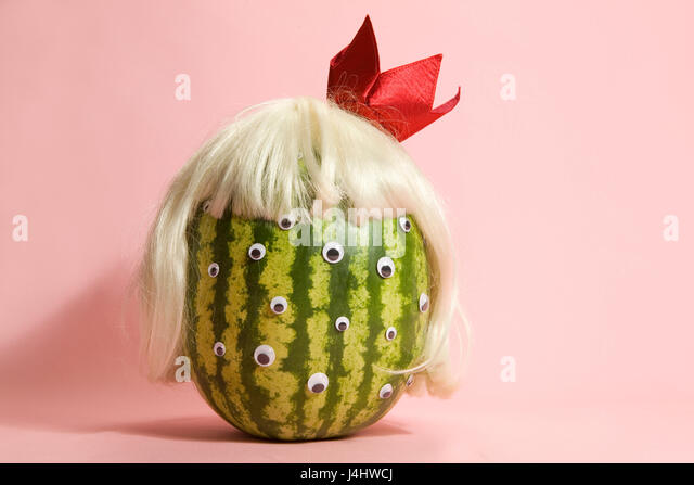 Freak watermelon wearing a wig and crown on a pink background - Stock Image