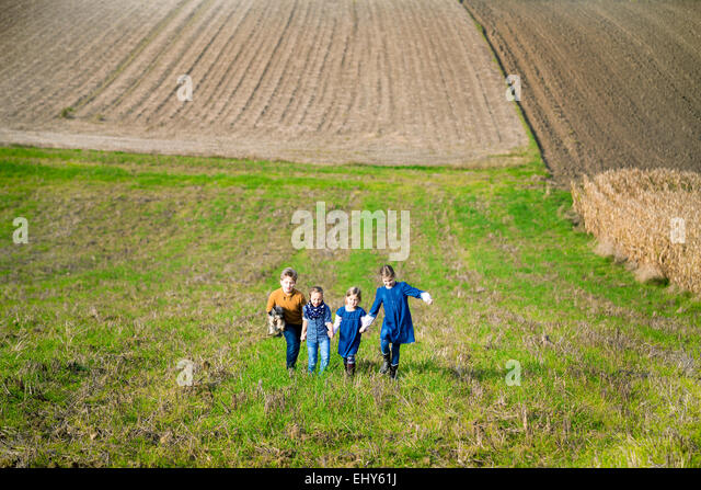 Four children walking in field - Stock Image