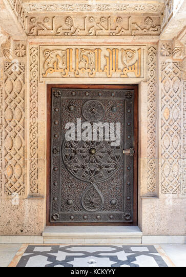 Closed wooden aged door with ornate bronzed floral patterns at the mosque of The Manial Palace of Prince Mohammed - Stock Image