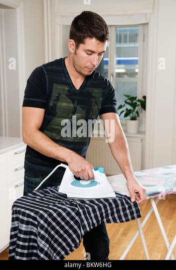 Young man ironing - Stock-Bilder