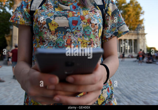 Madrid, Spain. 25th July, 2016. A girl pictured playing 'Pokemon Go' during a gathering at Retiro Park in - Stock-Bilder