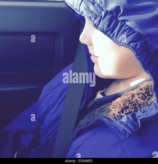 Profile of young boys face partially obscured by jacket hood - Stock Image