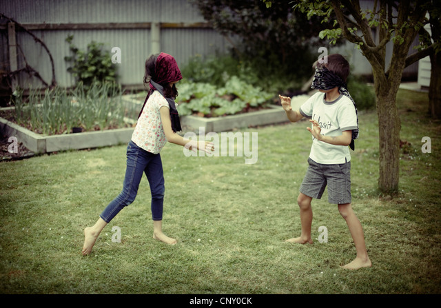 Children play wearing blinfolds. - Stock Image
