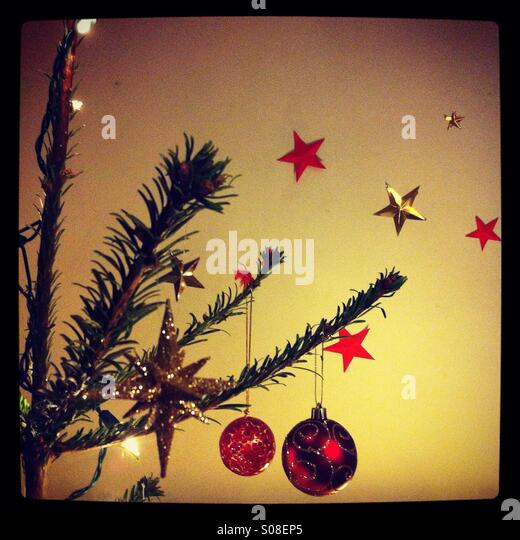 Detail of a Christmas tree decorated with baubles and fairy lights, with red and gold stars in the background - Stock Image