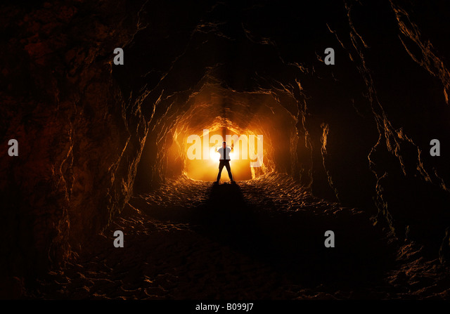 A man stands profile view at the end of a dark cave like tunnel where there is a bright light emanating from behind - Stock Image