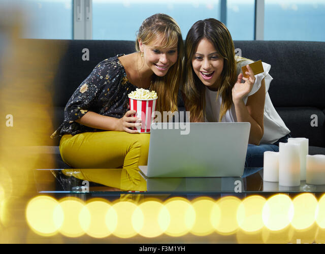 Two hispanic female friends sitting on sofa at home, looking at laptop computer and bidding online to buy an item. - Stock Image