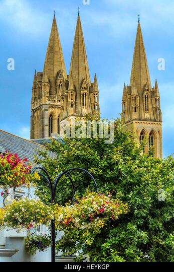 A view of Truro Cathedral spires from behind trees and flowers. - Stock Image