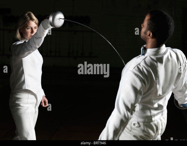 Two fencers, a young woman and a young man, in a confrontation - Stock Image