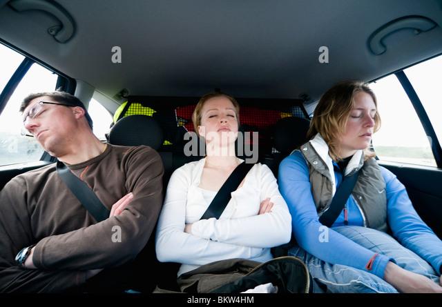 Three people sleeping in backseat of car - Stock-Bilder