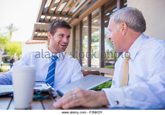Caucasian businessmen talking at cafe - Stock Image