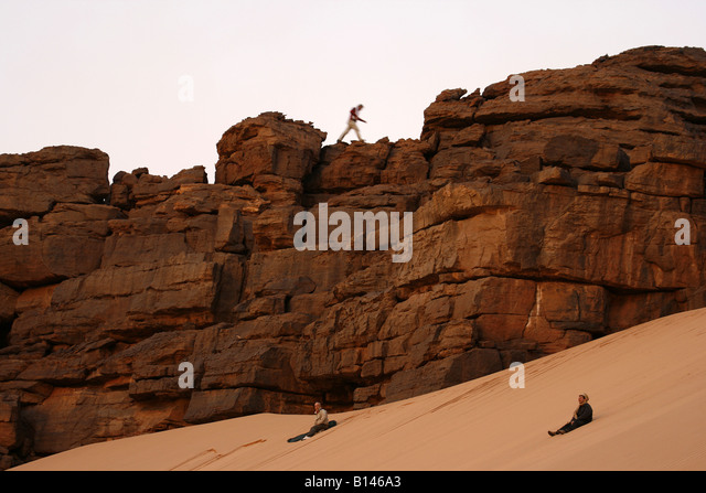 Tourists enjoying in Oued Tin Tarabine Tassili Ahaggar at sunset Algeria - Stock Image