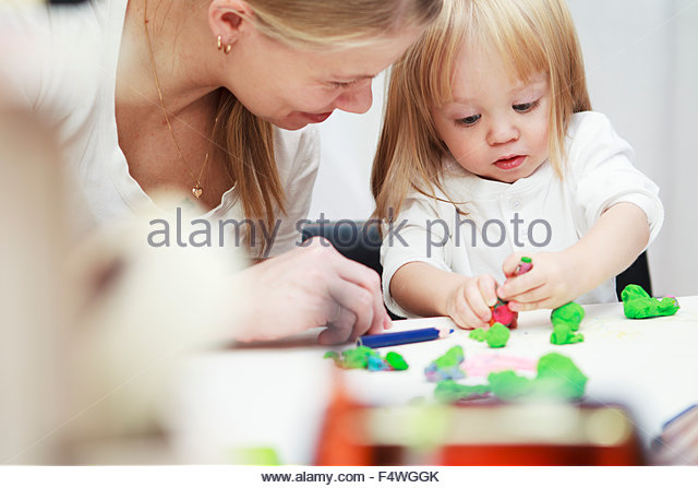 Little girl (2-3) playing with child's play clay - Stock Image