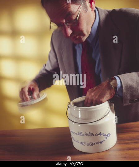man with hand in cookie jar - Stock Image