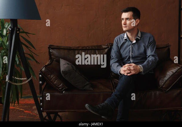 Pensive Middle Eastern man sitting on sofa - Stock-Bilder