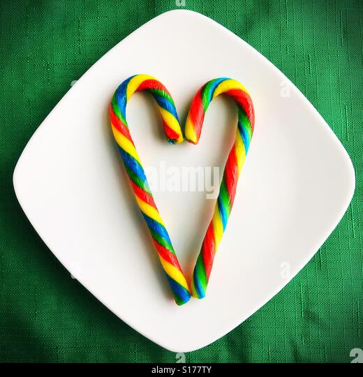 Two rainbow colored candy canes forming a heart on a platter. - Stock Image
