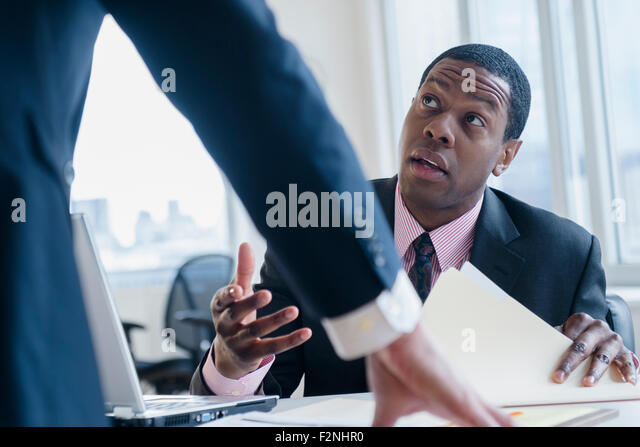 Businessmen talking at desk in office - Stock Image