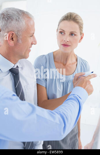 Businesswoman drawing graph on the board - Stock-Bilder