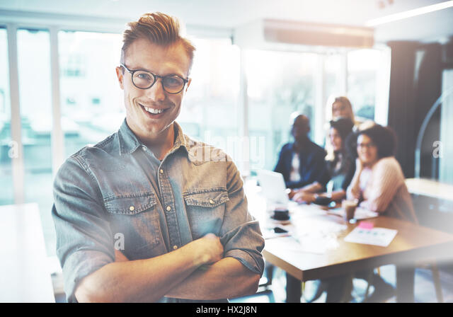 Portrait of a young confident man posing in front of his colleagues working at desk in a modern business office - Stock Image
