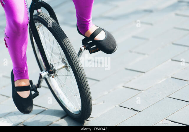 Low Section Of Woman Riding Bicycle On Street - Stock Image