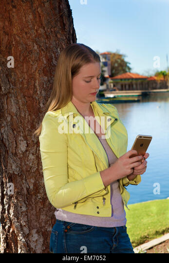 Caucasian 14-16 year old olds Teenage girl using iPhone  mobile  phone device outdoors  MR  © Myrleen Pearson - Stock-Bilder