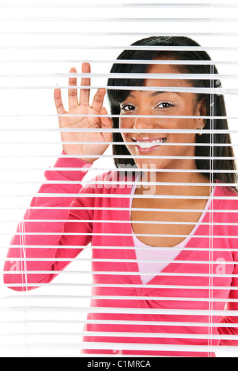 Happy young black woman looking through horizontal venetian blinds - Stock-Bilder