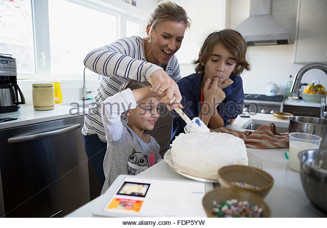 Family baking cake in kitchen - Stock Image
