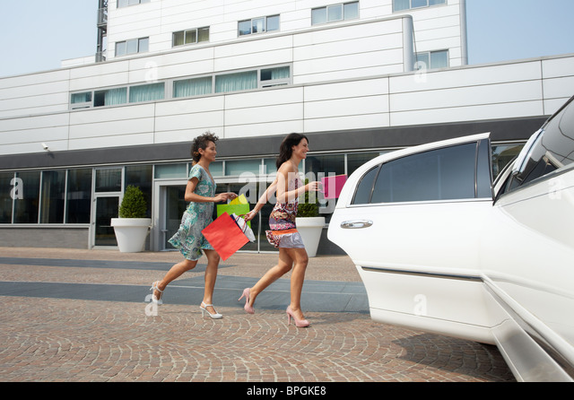 women running into car with shopping bags - Stock Image