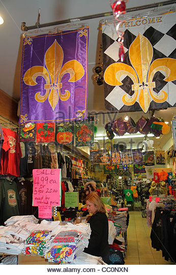 Louisiana New Orleans French Quarter souvenir store business shopping woman tee t-shirt banner fleur de lis symbol - Stock Image