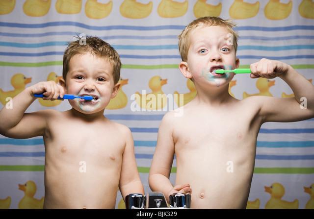 Two boys brushing teeth in bathroom sink - Stock-Bilder