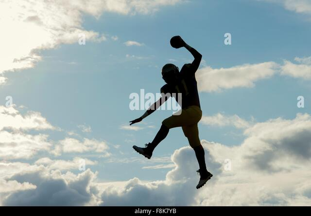 Teenage american football player, jumping with ball, mid air - Stock Image