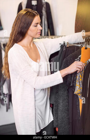 Female sales person arranging cloths in boutique - Stock Image