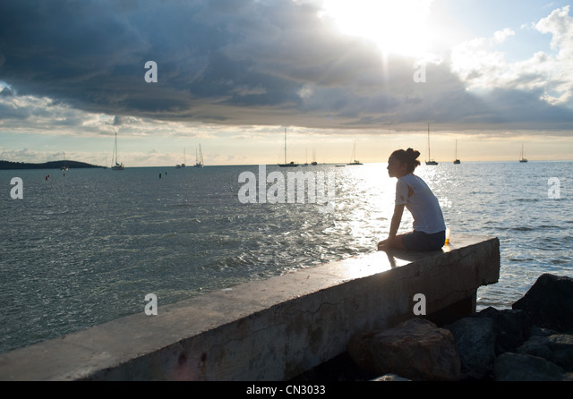 Woman sitting alone by the ocean - Stock Image