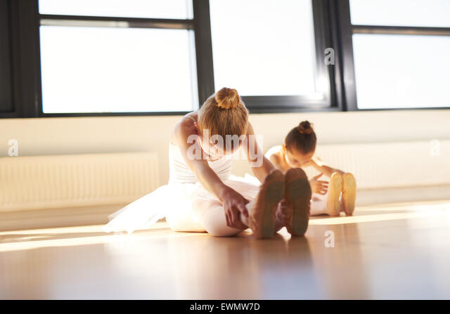 Two Young Ballerinas Doing an Exercise, Especially for their Legs, Inside the Studio Before the Actual Dance Rehearsal. - Stock Image
