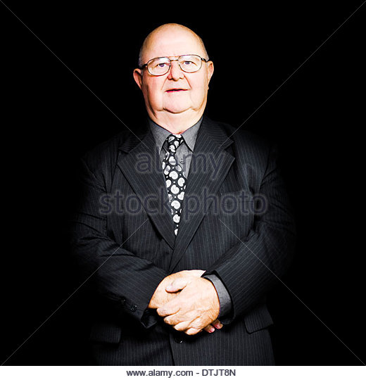 Isolated studio portrait of a senior business man wearing glasses and suit, in a big boss and general manager concept - Stock Image