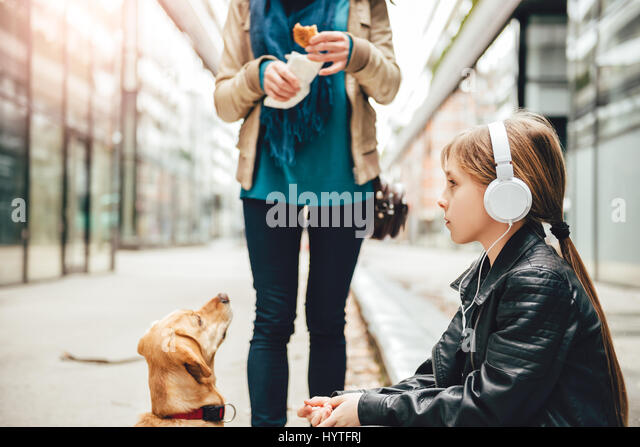 Daughter listening music on headphones while mother and her dog standing beside - Stock Image