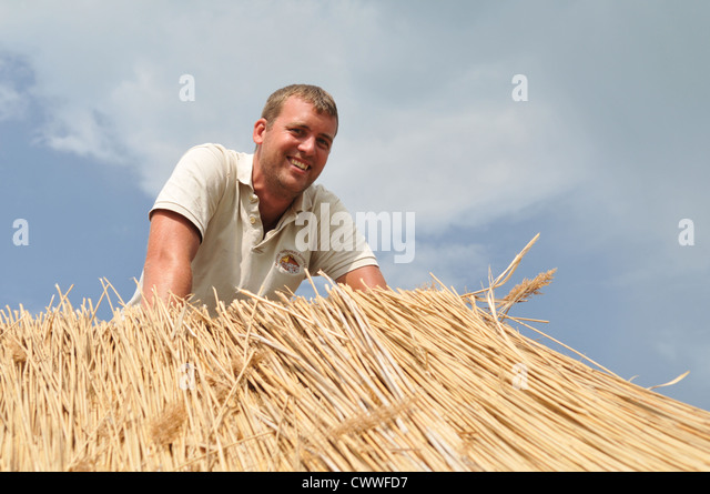 Man working on straw roof - Stock Image