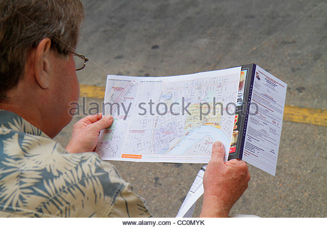 Louisiana New Orleans Louis Armstrong New Orleans International Airport MSY bus stop man holding map reading direction - Stock Image
