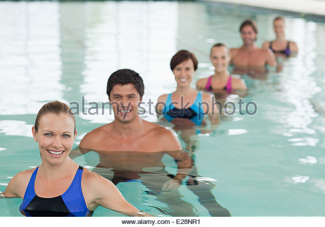 Portrait of smiling people in a row in swimming pool - Stock Image