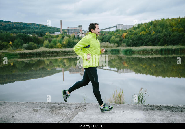 Man at the lake running on conrete path - Stock-Bilder
