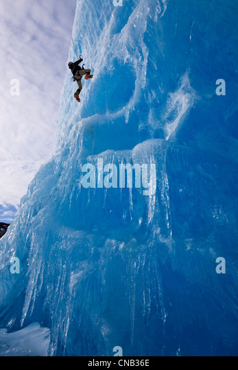 An ice climber ascends the face of a large iceberg frozen into Mendenhall Lake, Juneau, Southeast Alaska, Winter - Stock Image