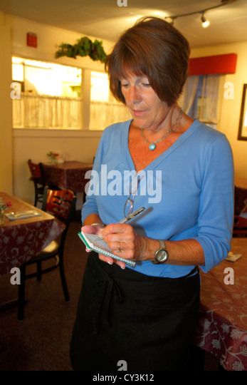 Maine Freeport The Corsican Restaurant mature woman waitress writing taking order service employee job - Stock Image