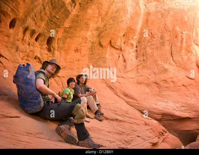 A Group Of Adventure Athletes Exploring Utah Slot Canyons; Hanksville Utah United States Of America - Stock Image