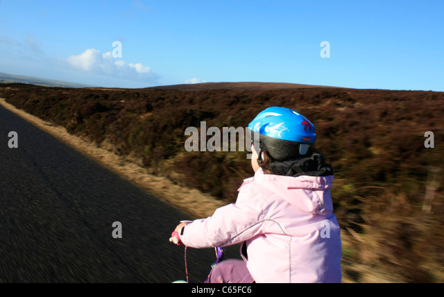 Young child cycling on a single track road - Stock Image