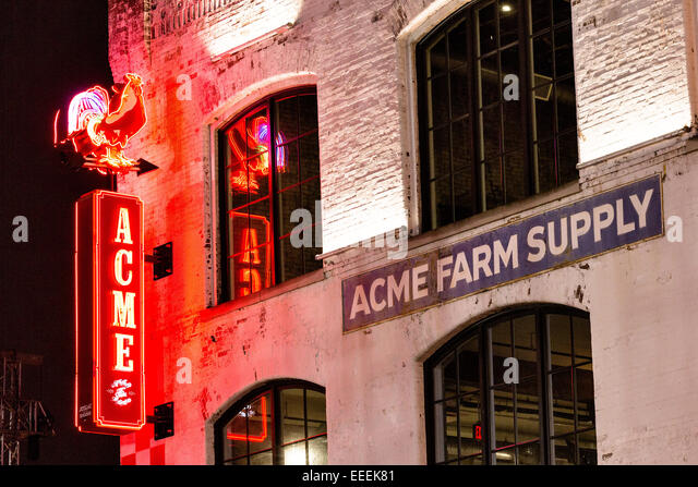 Neon sign for Acme Farm Supply restaurant on lower Broadway in Nashville, TN. - Stock Image