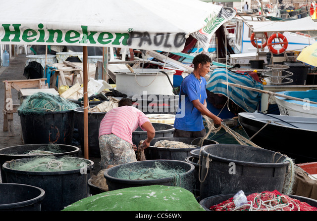 fishermen sorting their nets after a days fishing from anzio harbour - Stock Image